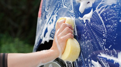 A Hand washing a blue car with a sponge